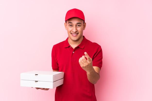 Молодой латинский человек доставки пиццы изолирован, указывая пальцем на вас, как будто приглашая подойти ближе.