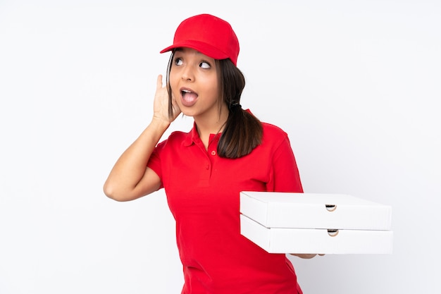 Young pizza delivery woman over isolated white wall listening to something by putting hand on the ear