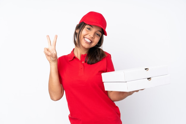 Young pizza delivery woman over isolated white wall showing victory sign with both hands