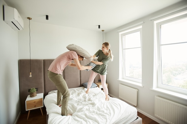 枕でお互いを破って遊び心のあるカップル