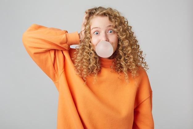 Молодая игривая кудрявая блондинка, одетая в теплый оранжевый свитер большого размера, стоит с рукой возле головы