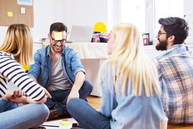 Молодая игривая счастливая группа людей, сидящих на полу офиса, играя угадайте записку.
