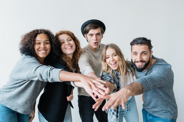 カジュアルウェアの若い遊び心のある異文化の友達が腕を前に伸ばしながら笑顔であなたを見て