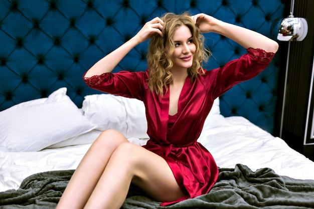 고급 호텔에서 포즈를 취하는 젊은 장난스런 관능적 인 여자, 실크 가운, 부드러운 톤의 색상을 입고 편안한 아침을 즐기십시오. 편안한 내실 분위기.