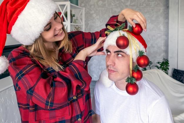 クリスマスツリーの代わりにクリスマスボールで男を飾るのを騙している若い遊び心のある女性サンタの帽子と赤いパジャマを着て怒っているカップルを見ている男