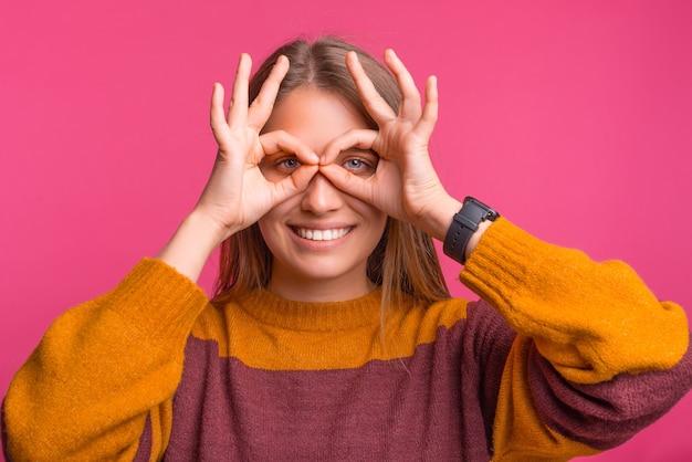 장난기 많은 젊은 여성이 분홍색 배경 위에 쌍안경 제스처를 하고 있습니다.