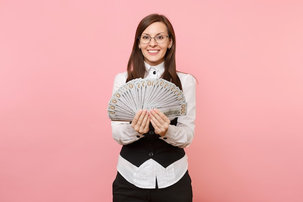 Young pleasant beautiful business woman in glasses holding bundle lots of dollars, cash money isolated on pink background. lady boss. achievement career wealth concept. copy space for advertisement.
