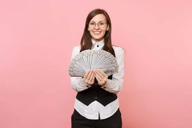 Молодая приятная красивая деловая женщина в очках, держащая пачку долларов, наличные деньги, изолированные на розовом фоне. леди босс. концепция богатства карьеры достижения. скопируйте место для рекламы.