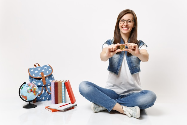 Young pleasant beautiful casual woman student in glasses holding bitcoin sitting near globe, backpack, school books isolated