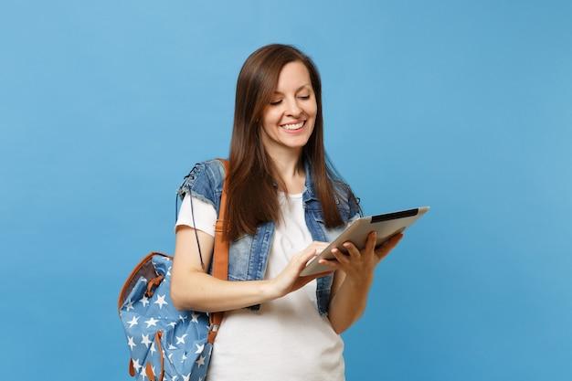 파란색 배경에 격리된 태블릿 pc 컴퓨터를 들고 배낭을 메고 데님 옷을 입은 젊고 아름다운 여학생입니다. 대학에서 교육입니다. 광고 공간을 복사합니다.