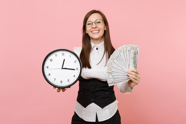 Young pleasant business woman in glasses holding bundle lots of dollars, cash money and alarm clock isolated on pink background. lady boss. achievement career wealth. copy space for advertisement.