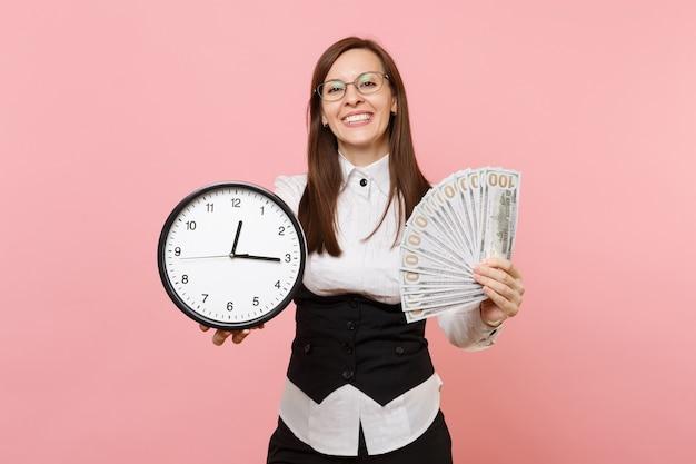 분홍색 배경에 격리된 많은 달러, 현금, 알람 시계를 들고 안경을 쓴 젊고 유쾌한 비즈니스 여성. 여사장님. 성취 경력 부입니다. 광고 공간을 복사합니다.