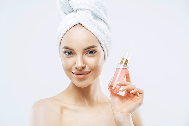Young pleasant looking woman uses perfum, likes new smell, stands delighted indoor, applies makeup, has healthy skin wears bath towel isolated on white wall has glamorous look. pleasant smelling