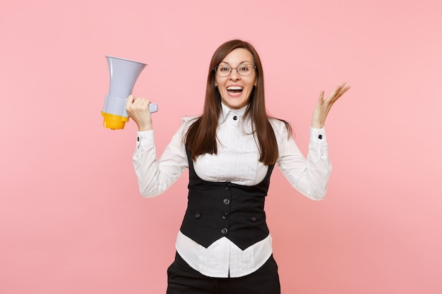 Young pleasant pretty business woman in suit, glasses holding megaphone spreading hands isolated on pastel pink background. lady boss. achievement career wealth concept. copy space for advertisement.