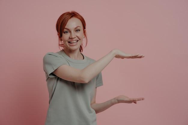 Молодая приятная рыжеволосая женщина с руками показывает огромный размер продукта или что-то большое