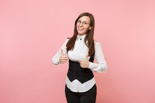 파스텔 핑크색 배경에 고립된 엄지손가락을 보여주는 검은 양복과 안경을 쓴 젊고 성공적인 비즈니스 여성. 여사장님. 성취 경력 부 개념입니다. 광고 공간을 복사합니다.