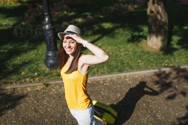 여행가방을 들고 모자를 쓴 젊고 유쾌한 여행자 관광 여성은 이마 근처에서 손을 잡고 도시 야외에서 산책을 하고 있습니다. 주말 휴가를 여행하기 위해 해외로 여행하는 소녀. 관광 여행 라이프 스타일.