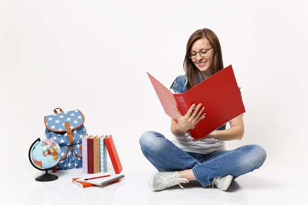 Young pleasant woman student in glasses holding looking on red folder for papers document near globe, backpack, school books isolated