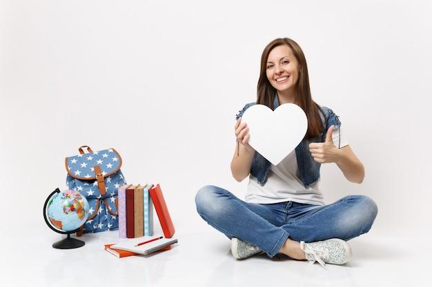 Студент молодой приятной женщины держит белое сердце с копией пространства, показывая большой палец вверх, сидя рядом с земным шаром, рюкзаком, школьными учебниками, изолированными на белой стене