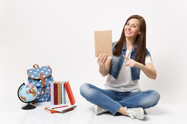 Молодая приятная студентка в джинсовой одежде, указывая указательным пальцем на книгу, сидя возле рюкзака глобус, изолированные школьные учебники