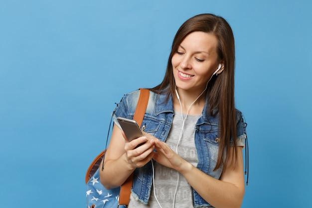 Молодой приятный студент женщины в джинсовой одежде с рюкзаком и наушниками, слушая музыку, держащуюся с помощью мобильного телефона, изолированного на синем фоне. обучение в университете. скопируйте место для рекламы.
