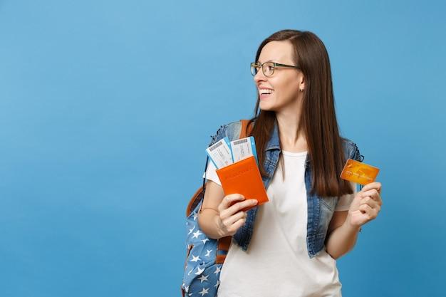 Молодой приятный студент женщины с рюкзаком смотрящим кредитной картой билетов посадочного талона паспорта владения изолированной на синем фоне. обучение в вузе за рубежом. концепция полета авиаперелета.