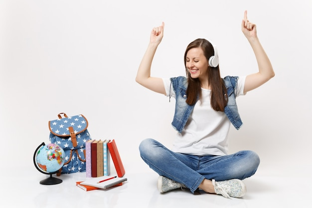 Young pleasant woman student with headphones listen music pointing index fingers up sitting near globe, backpack school books isolated