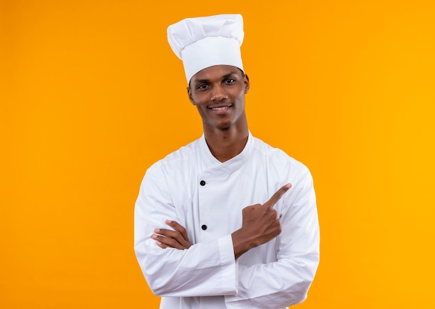 Young pleased afro-american cook in chef uniform crosses arms and points to the side isolated on orange wall