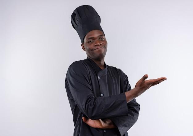Il giovane cuoco afroamericano soddisfatto in uniforme del cuoco unico attraversa le braccia e indica a lato con la mano su bianco con lo spazio della copia