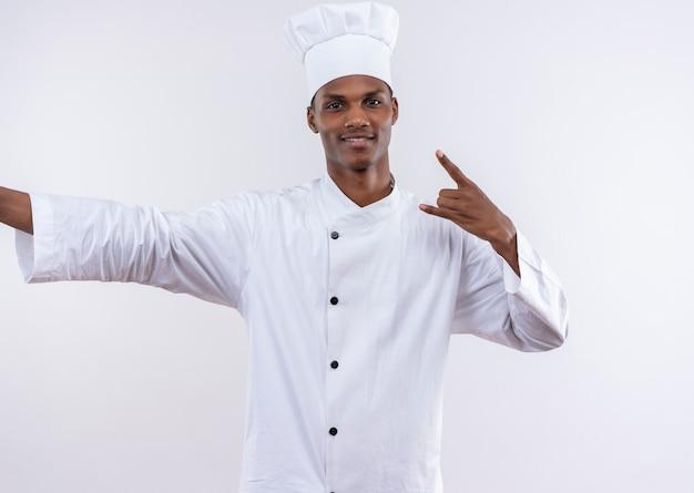 Giovane cuoco afroamericano felice in corna di gesti uniformi del cuoco unico con la mano isolata sulla parete bianca