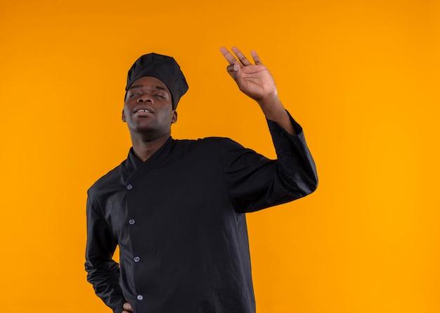 Giovane cuoco afroamericano contento nel segno giusto della mano di gesti uniformi dello chef isolato su priorità bassa arancione con lo spazio della copia