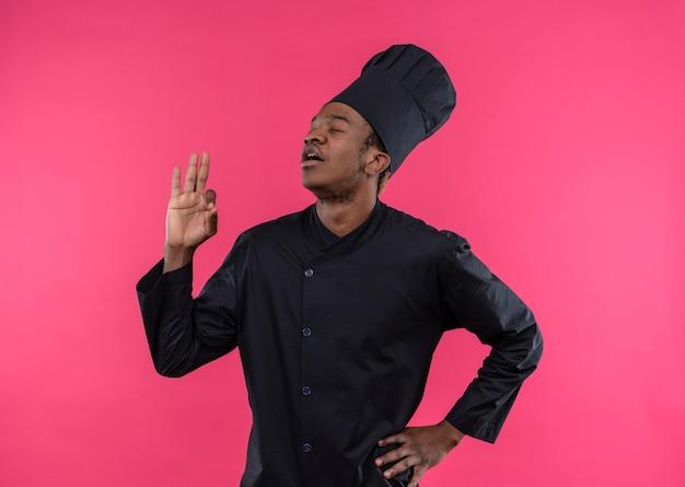Giovane cuoco afroamericano contento nel segno giusto della mano di gesti dell'uniforme del cuoco unico isolato sulla parete rosa