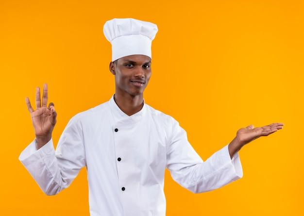 Il giovane cuoco afroamericano felice in uniforme da chef gesticola ok e tiene la mano dritta isolata sulla parete arancione