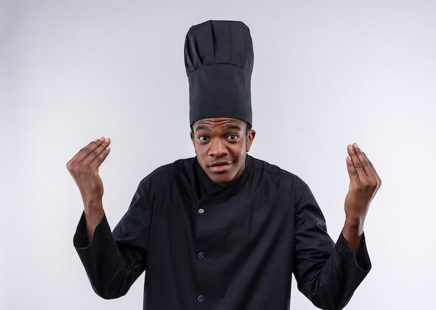 Il giovane cuoco afroamericano felice in gesti uniformi dello chef aspetta il segno della mano isolato sulla parete bianca