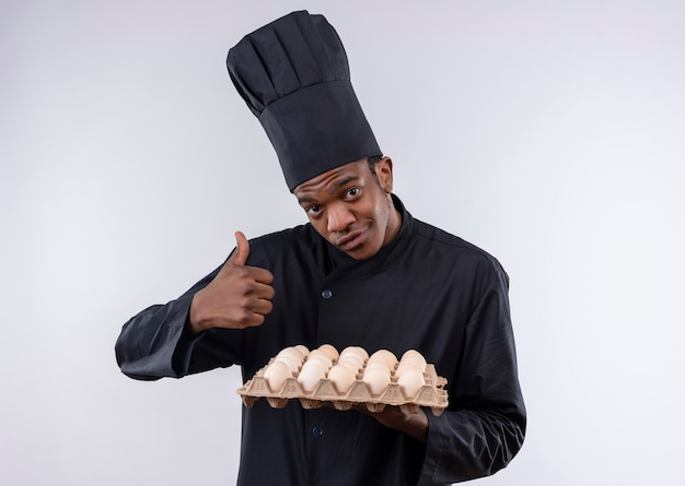 Young pleased afro-american cook in chef uniform holds batch of eggs and thumbs up isolated on white wall