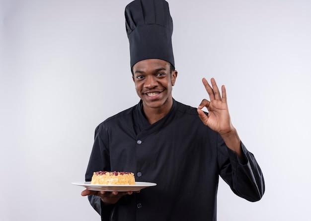 Il giovane cuoco afroamericano felice in uniforme dello chef tiene la torta sul piatto e gesti il segno giusto della mano isolato sulla parete bianca