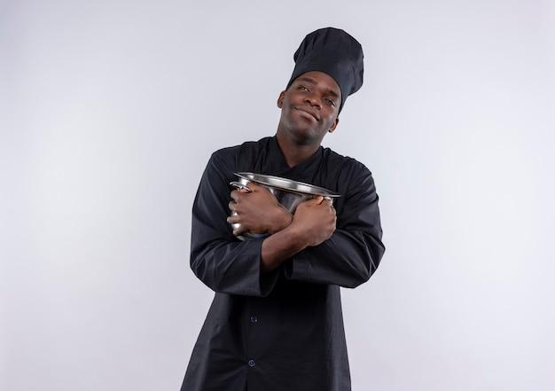 Il giovane cuoco afroamericano soddisfatto in uniforme del cuoco unico tiene la casseruola e guarda a lato su bianco con lo spazio della copia Foto Gratuite