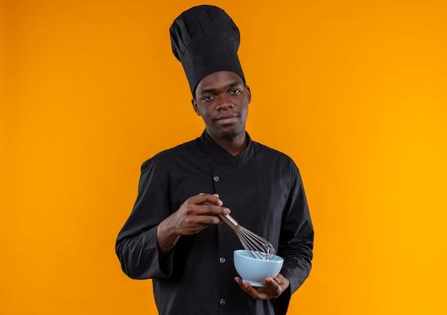 Il giovane cuoco afroamericano felice in uniforme dello chef tiene la frusta e la ciotola isolata su fondo arancio con lo spazio della copia