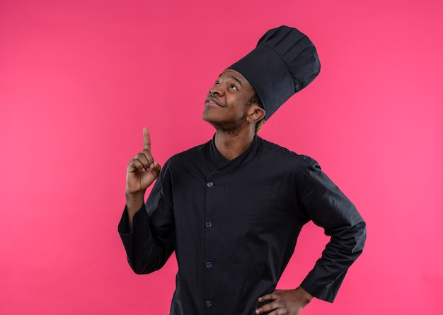 Young pleased afro-american cook in chef uniform points up and puts hand on waist isolated on pink wall