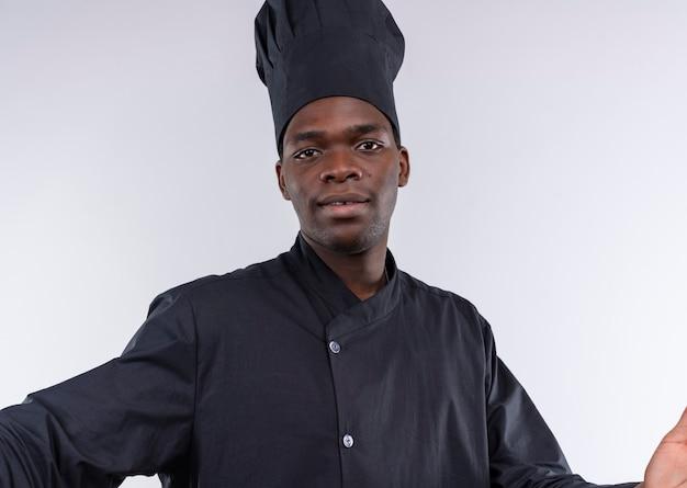 Il giovane cuoco afroamericano soddisfatto in uniforme del cuoco unico finge di tenere la macchina fotografica isolata su fondo bianco con lo spazio della copia