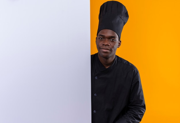 Young pleased afro-american cook in chef uniform stands behind white wall isolated on orange space with copy space