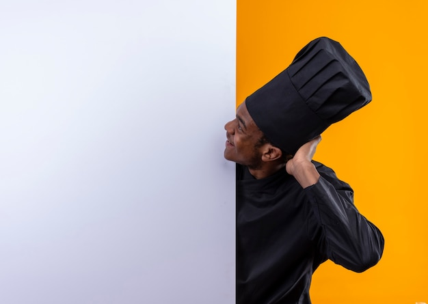 Young pleased afro-american cook in chef uniform stands behind white wall and looks at wall isolated on orange wall