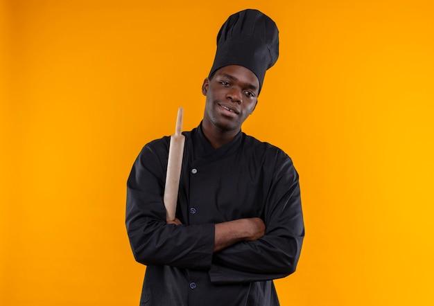 シェフの制服を着た若い喜んでアフリカ系アメリカ人の料理人は腕を組んで、コピースペースでオレンジ色の背景に分離された麺棒を保持します