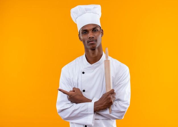 シェフの制服を着た若い喜んでいるアフリカ系アメリカ人の料理人が腕を組んで、オレンジ色の壁に隔離された麺棒を保持します