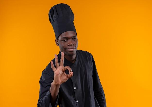 若いは、シェフの制服のジェスチャーでアフリカ系アメリカ人の料理人を喜ばせます。コピースペースでオレンジ色の背景に分離された手のサイン