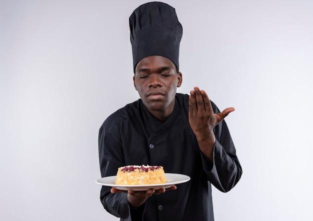 シェフの制服を着た若いアフリカ系アメリカ人の料理人が、コピースペースのある白い皿にケーキの匂いを嗅ぐふりをします。