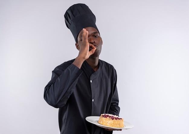 シェフの制服を着た若い喜んでアフリカ系アメリカ人の料理人は、プレートにケーキを保持し、コピースペースで白のおいしい手サインをジェスチャーします