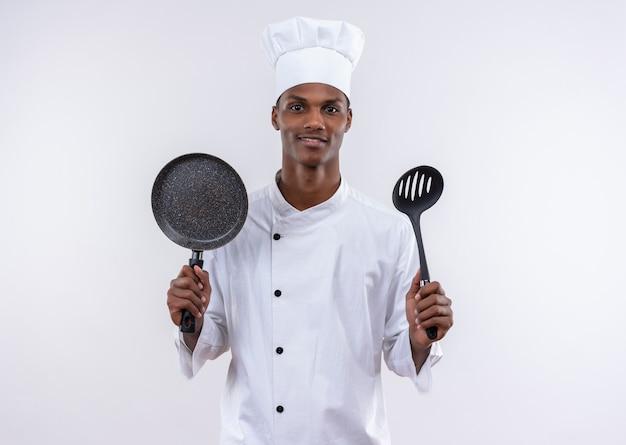 シェフの制服を着た若い喜んでアフリカ系アメリカ人の料理人は、孤立した白い壁にフライパンとヘラを保持します