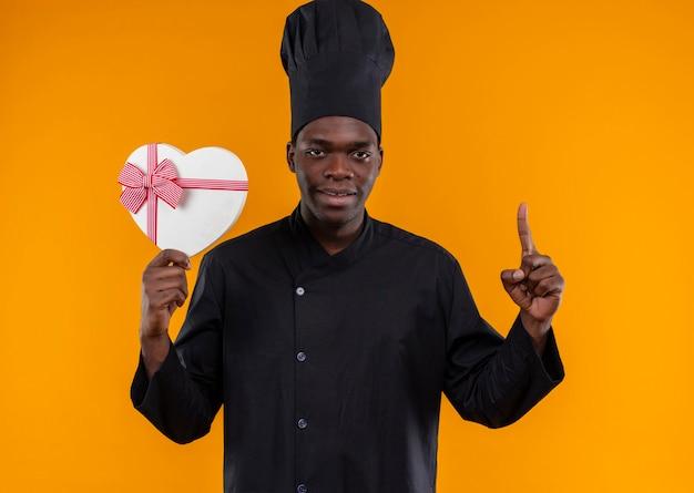 シェフの制服を着た若い喜んでいるアフリカ系アメリカ人の料理人は、ハート型のボックスを保持し、コピースペースでオレンジ色を指しています