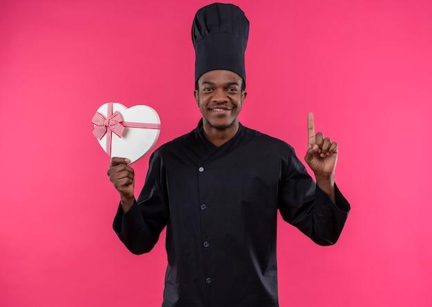 シェフの制服を着た若い幸せなアフリカ系アメリカ人の料理人は、ピンクの壁に隔離されたハート型のボックスと親指を保持します